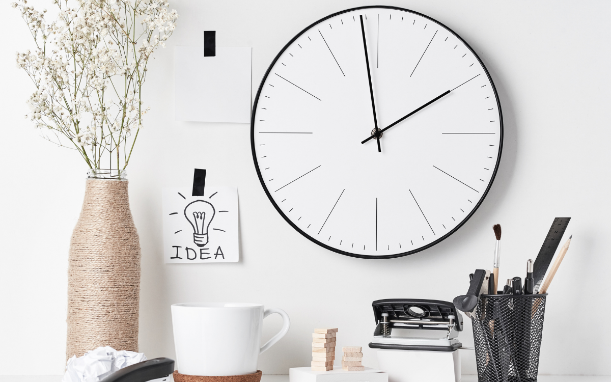 Desk with clock on the wall - representing duration of qualitative market research recruitment.
