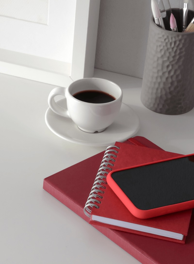 Red book, notebook and phone on work table with coffee